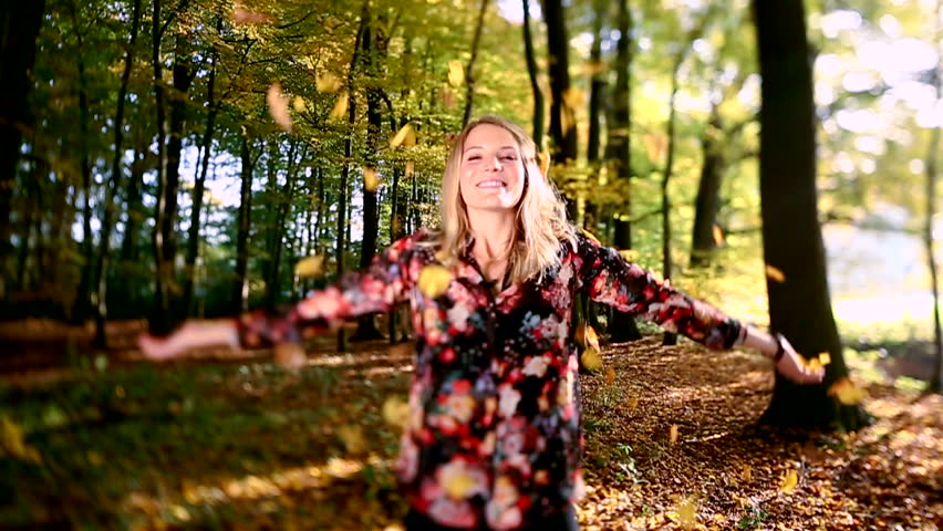 Girl throwing leaves in Autumn in slow motion, smiling into the camera