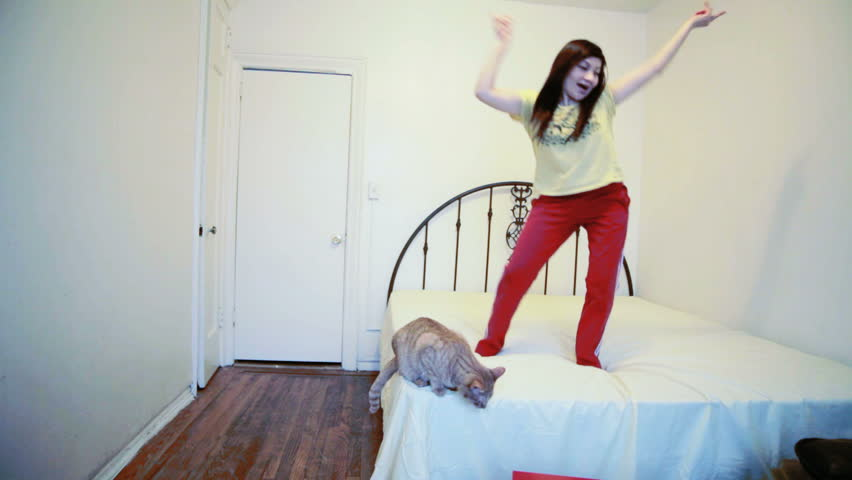 White girl jumping on the bed in her bedroom | Shutterstock HD Video #3578771