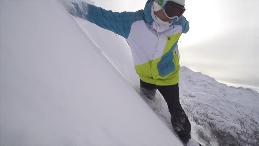 SLOW MOTION: snowboarder carving in powde