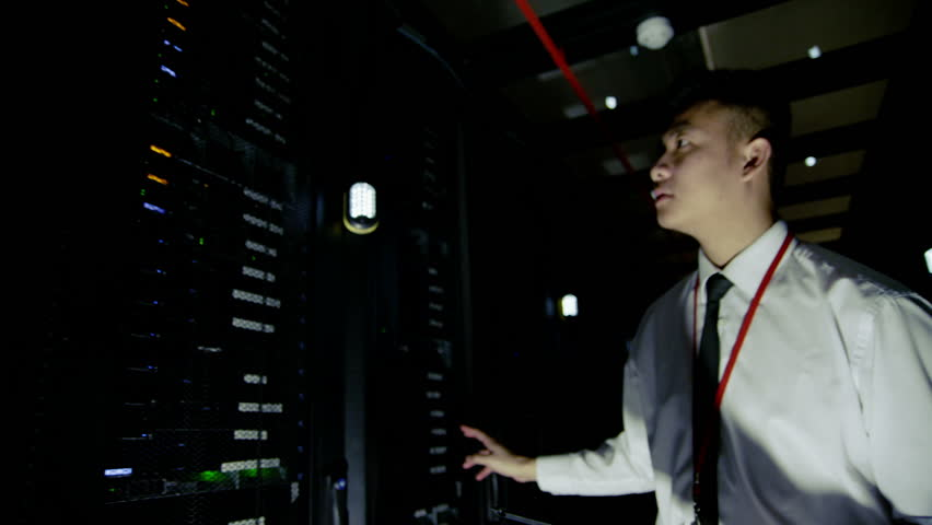 A young male IT engineer of Asian ethnicity is working in a data center with rows of server racks and super computers. He is looking into cabinets and checking cables and other equipment. Slow motion.