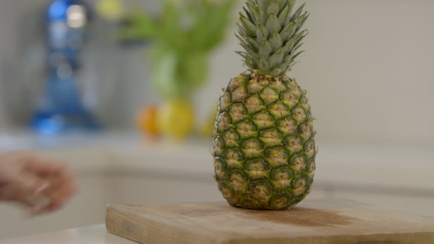 Close shot of woman cutting pineapple in modern kitchen, low depth of field