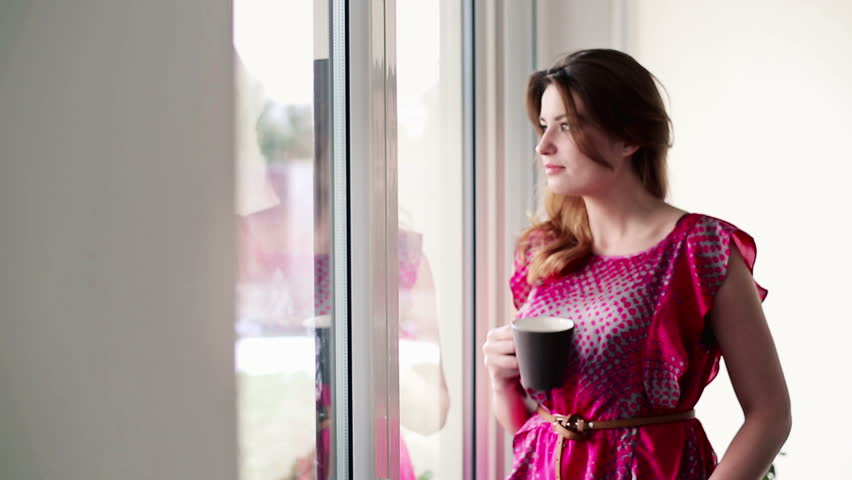 Beautiful woman in drinking tea by the window at home