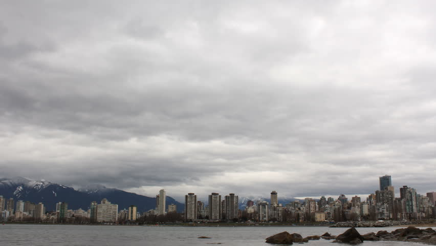 Vancouver Skyline Time Lapse. A time lapse view across English Bay, the apartments and condominiums of the West End, and the snow capped North Shore Mountains in Vancouver, British Columbia, Canada.  | Shutterstock HD Video #3624698