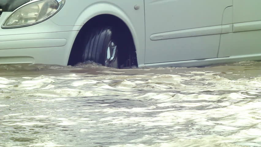 Flooded road after heavy rains,cars moving slowly in deep waters. vehicle sequence.