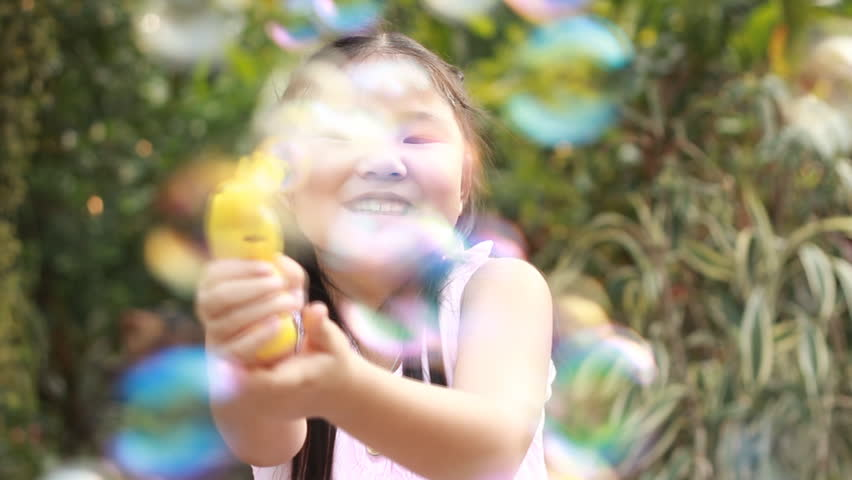 A  Little Girl Playing with Soap Bubbles, Outdoor Having Fun