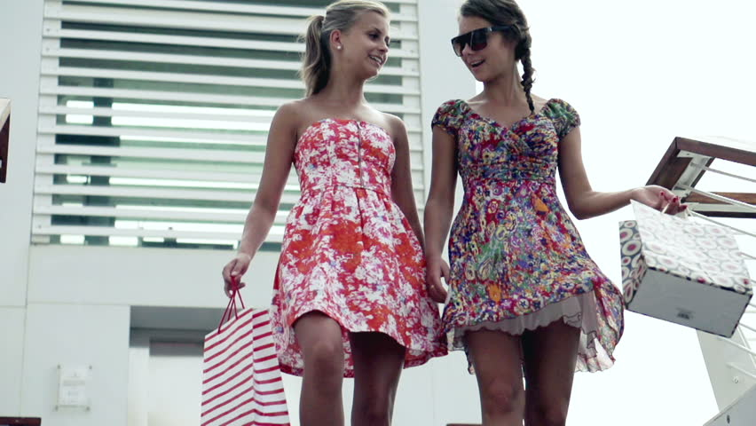 Female friends after shopping descending the stairs, slow motion shot at 240fps