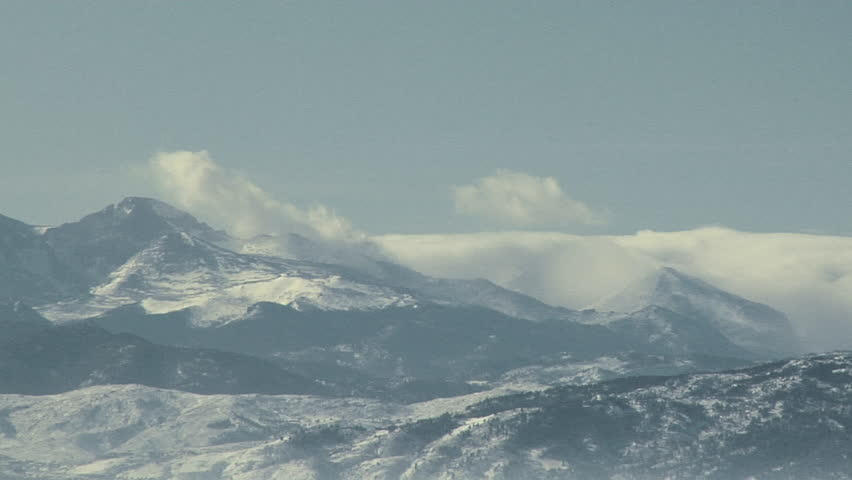 Stormy Peaks. Hurricane force winds lash clouds and snow cover atop Long's Peak in Colorado on mid-winter day.