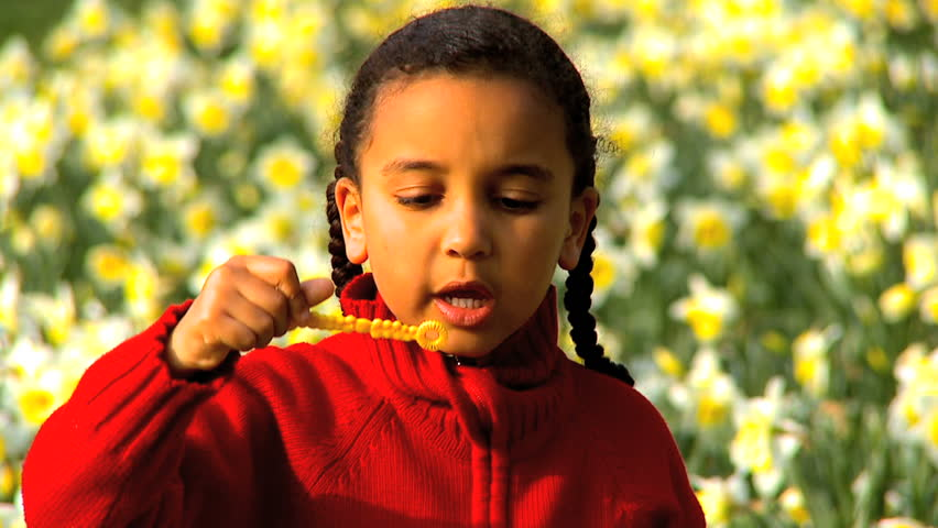 Cute african american child blowing soap bubbles in a field of flowers