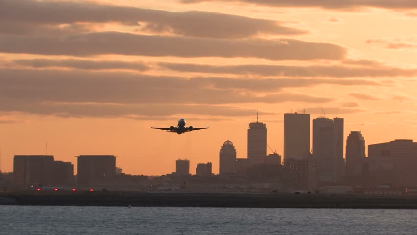 Airplane takeoff from Logan Airport, Boston at sunset camera follows