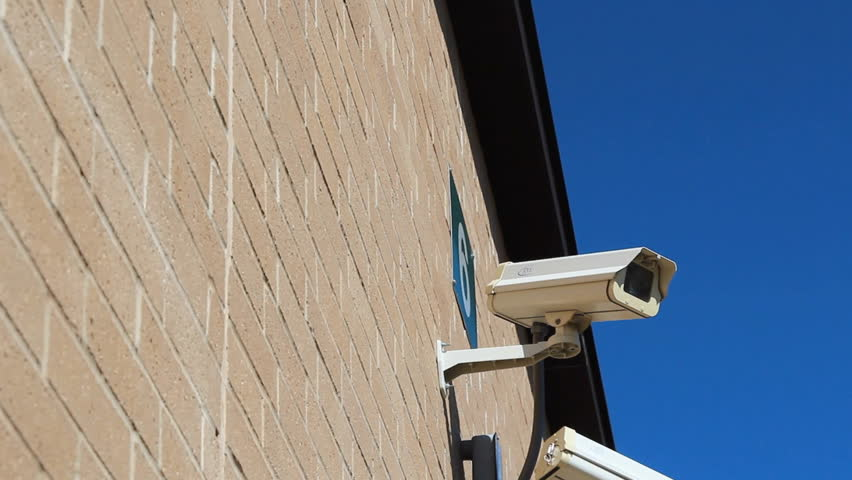 Two security cameras on a brick elementary school, looking out over a parking lot.