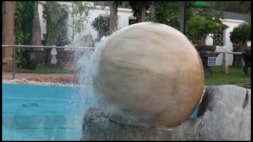 Spinning Ruby Stone with Water: A heavy round granite stone is amazingly spinned by the nimble  power of water. Located at the Bonsai Garden, Sri Ganapathy Sachchidananda Ashrama. Mysore, India.