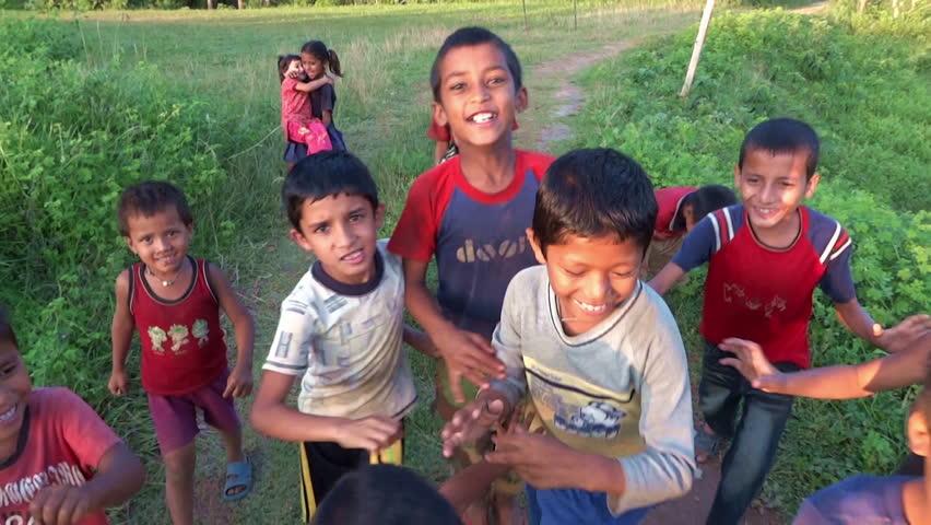 SARANKOT, NEPAL – CIRCA OCTOBER 2011 – Happy nepali and refugee tibetan children pursuing the camera circa October 2011 in Sarankot village in Nepal.
