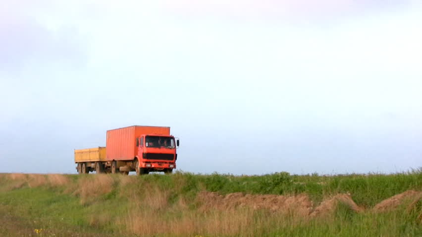 Big orange truck with a trailer passed and left on the steppe highway against