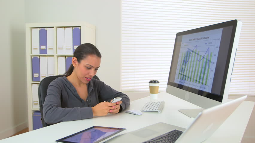 Happy Latina business woman excited at desk