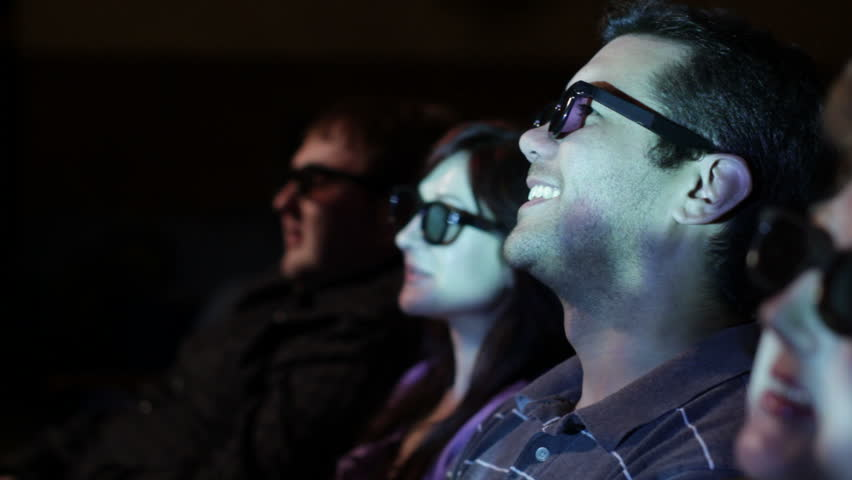 Young man watching a 3D movie with a group of friends, exchanging comments.