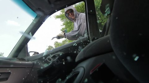 Burglar smashes a car window with a pry bar and reaches in to grab a bag with a laptop computer. Recorded with high shutter speed.