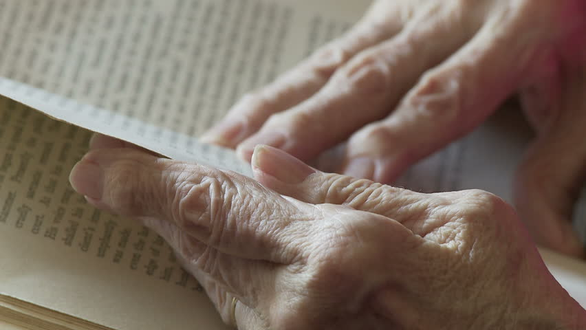 Elderly woman's hands, deformed by arthritis, turn the pages of an old book.