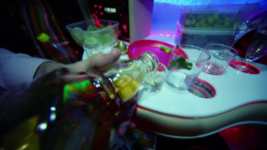 Man pours alcohol in small glasses at table in limo