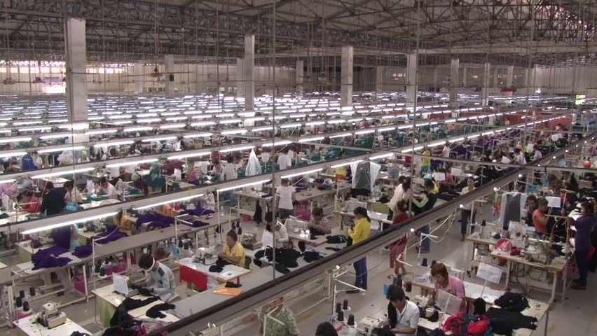 PHNOM PENH, CAMBODIA - CIRCA SEPTEMBER 2011 - superb high angle wide shot overview pan from left to right of large garment factory floor, with hundreds of unidentified garment workers below