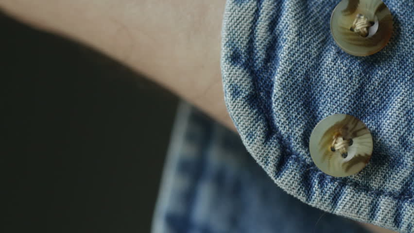 879c1f56a3 Close shot of hand doing up the button on the cuff of a denim shirt.