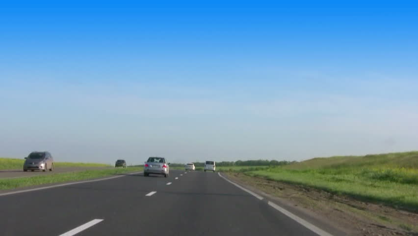 Sunny day. The viewer moves the car along the highway in the steppe