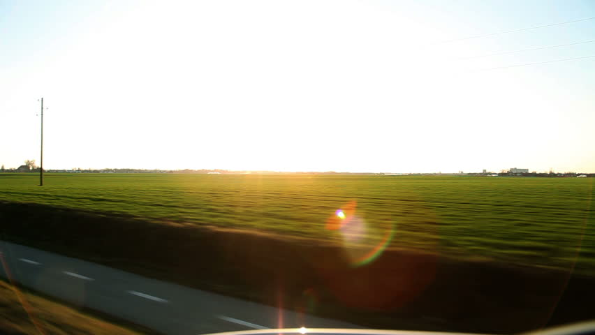 View from the car's side window while driving pov on highway with flare.