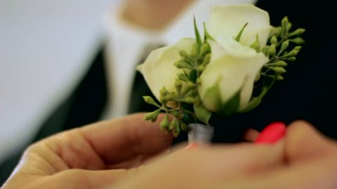 Close up of a woman pinning a corsage on a man in a black suit