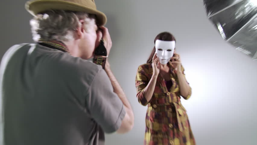 Photographer tries to reveal the person behind the mask as he takes pictures of female model Edgy, hand-held camera in studio.
