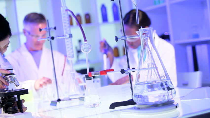 Medical students working with a microscope and test tubes in laboratory conditions