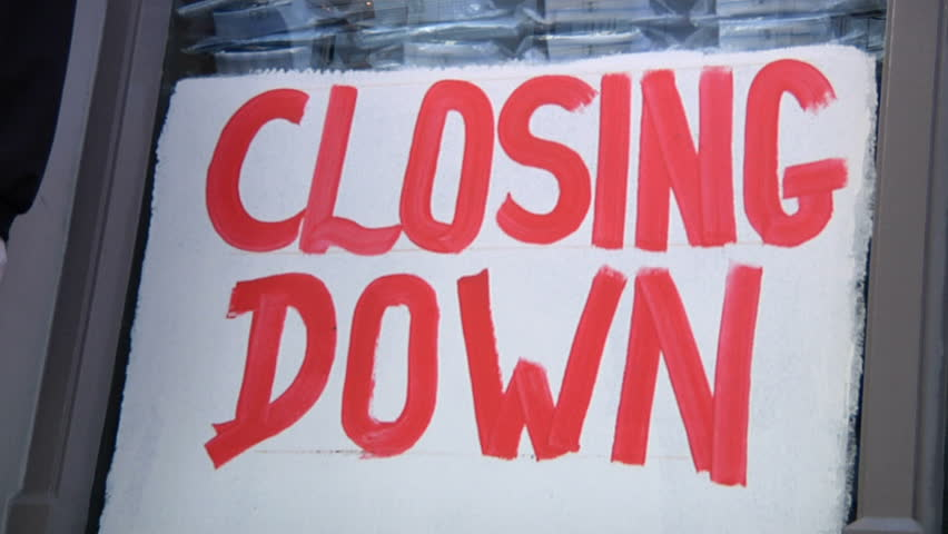Closing down sign in shop window - with people walking by