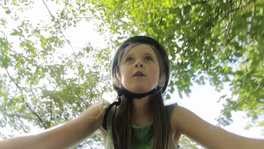 Child Cycling - A little girl with cycle helmet cycling under some trees in a park. (camera attached to handlebars) pov