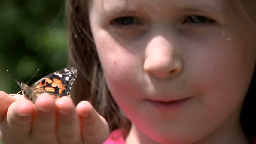 Little girl with butterfly on hand - painted lady