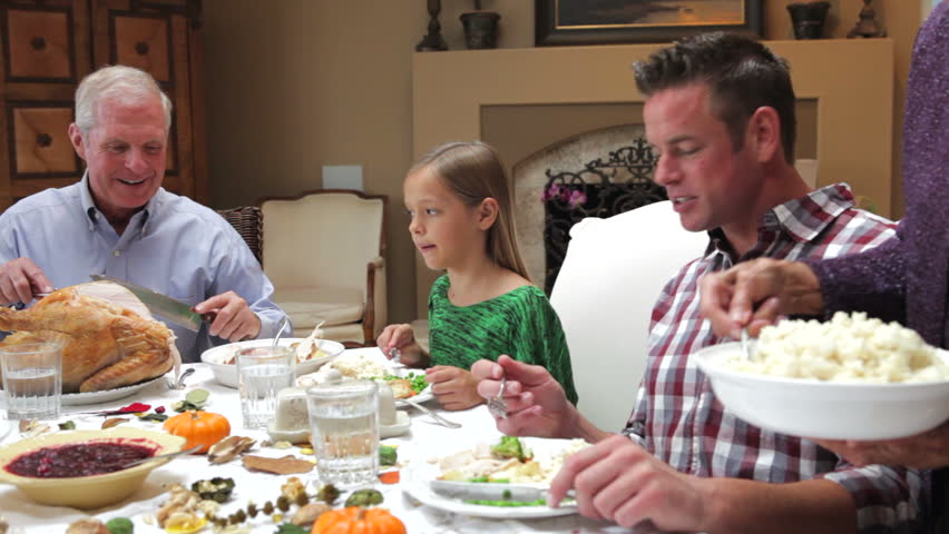 Camera tracks across table as grandfather carves slices of turkey at thanksgiving dinner. Shot on Canon 5d Mk2 with a frame rate of 30fps