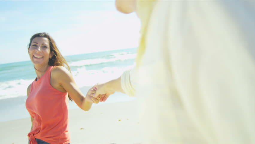 Happy Caucasian couple spending time together walking beach holding hands shot on RED EPIC