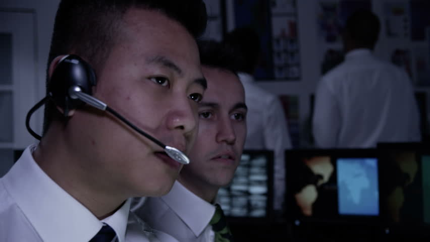 A team of security personnel man the stations within a busy system control room. Could be a weather or power station or air traffic control. It could be a  police/army control facility. Slow motion.