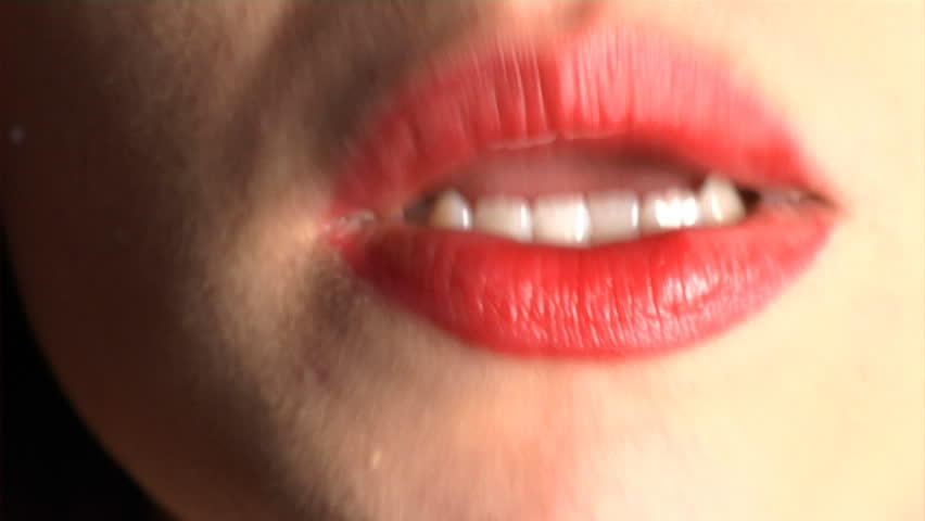 Lipstick Kiss - a young woman applies lipstick and then kisses the camera leaving a lipstick kiss