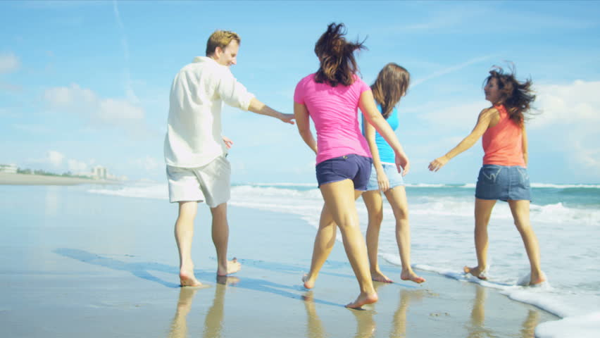 Caucasian teenage girls playing with parents in ocean shallows along sand on beach shot on RED EPIC | Shutterstock HD Video #3797708