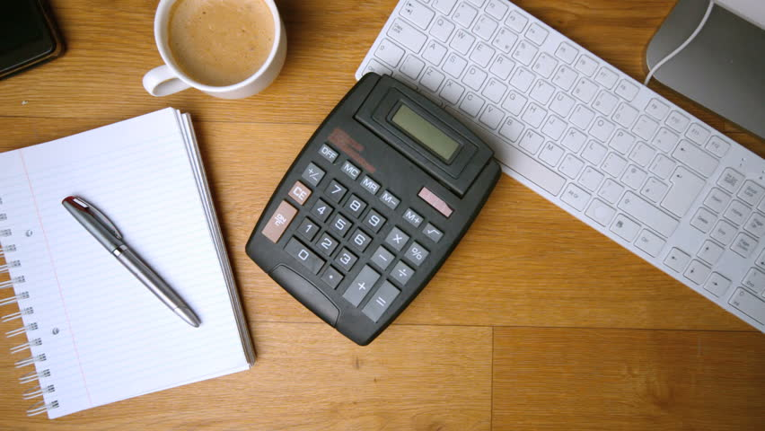 Calculator falling on office desk beside computer coffee cup and notepadin slow motion | Shutterstock HD Video #3808538