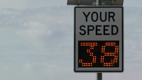 Road sign clocks vehicles speed as they drive by. 1080p