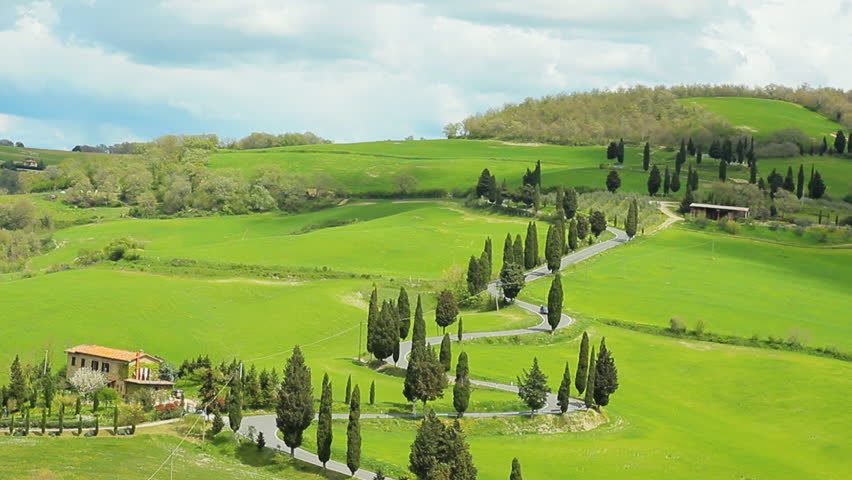 winding road with cypresses beside in tuscany val d'orcia montepulciano crane shot