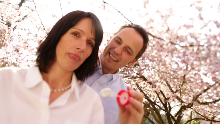 Attractive mature woman blowing soap bubbles in slow motion with her husband, the happy couple laughing under cherry blossoms