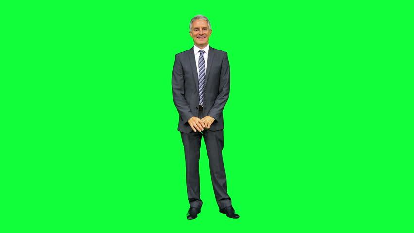 Mature male Caucasian businessman standing in front modern green screen environment