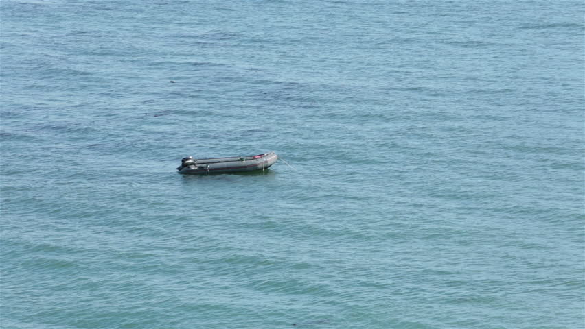 Ocean rubber diving boat anchored on water. Summer recreation and sport rubber boat anchored off coast of Northern California. Used for fishing and sport diving.
