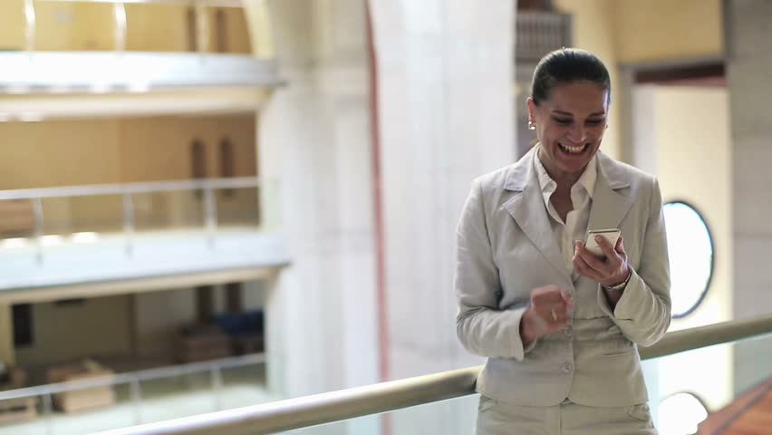 Successful businesswoman with smartphone in office building