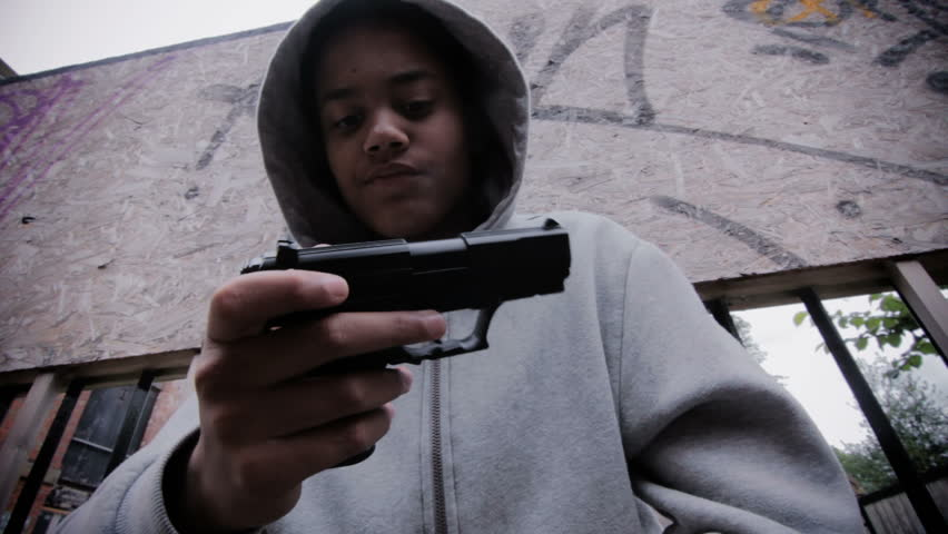 Teenage boy with a gun - wearing a hoodie