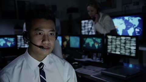 Security worker in a busy system control room is taking calls via a headset and either issuing or receiving instructions.