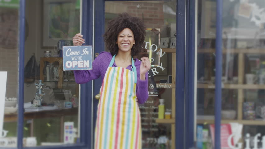 A happy and excited female shopkeeper stands outside of her small independent shop to welcome potential customers. She is holding an 'open' sign and wearing a colorful apron.