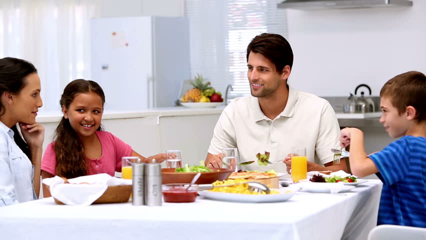 Family chatting and having dinner at home in kitchen