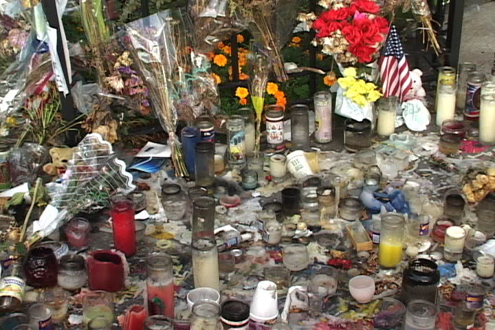 NEW YORK CITY - SEPTEMBER 29, 2001: Bouquets of flowers, American flags, and burned candles cover the ground in memory of 9/11.