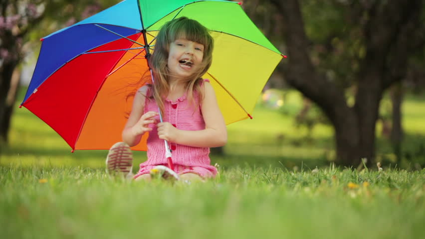 Cute girl with umbrella sitting on grass and laughing